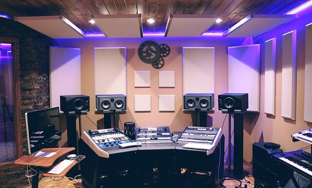 Studio with sound mixer, speakers and acoustic panels on wall and ceiling