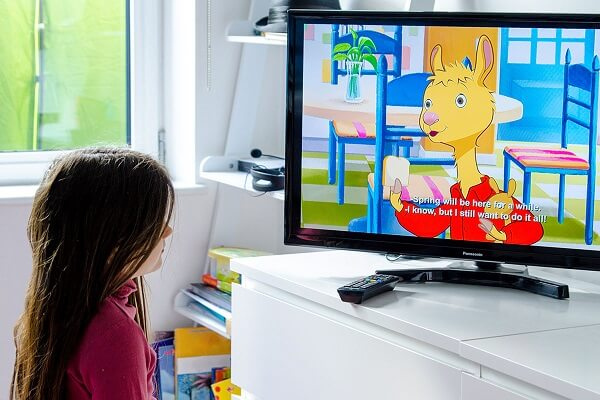 Young girl watching cartoons on TV with subtitles switched on