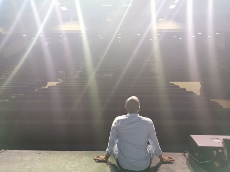 Ahmed sitting on the edge of the stage under spotlights and looking out at empty seats