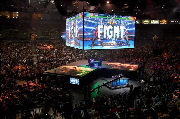 Photo of audience at EVO watching video games fighting match on big screen above a stage where the gamer is playing