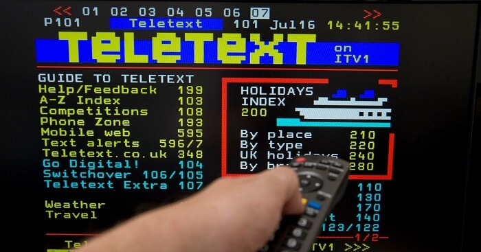 A person's hand holding a remote control pointing to the TV with Teletext on the screen