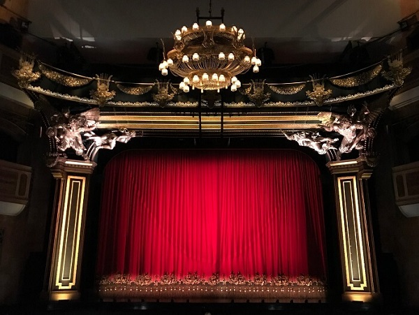 Theatre stage with red curtain drawn close