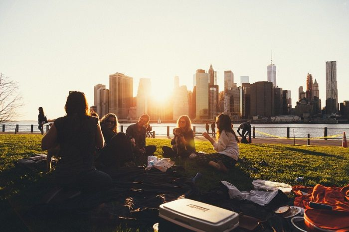 People sitting on grass beside river with sun shining over skyscrapers