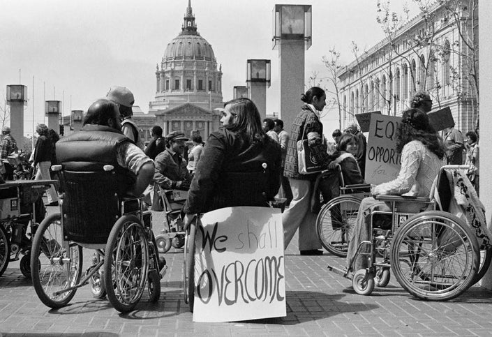 Black and white picture of group of wheelchair users at a 504 Sit-In in San Francisco with a sign behind one of them that says 'We Shall Overcome'