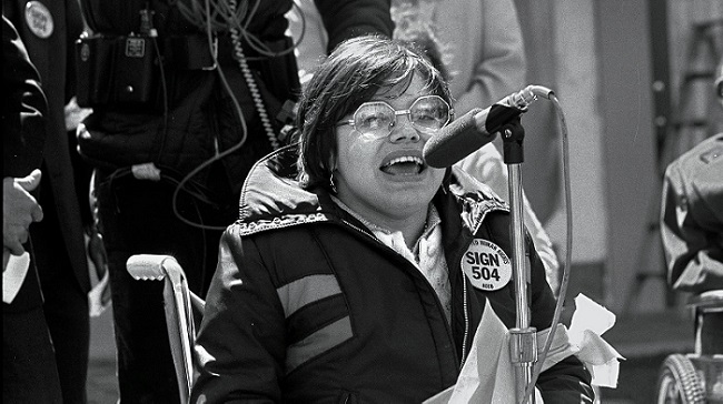 Black and white photo of activist Judy Heumann delivering a speech
