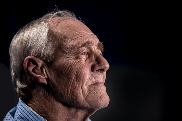 Photo of an elderly white male's side of his head, wearing a single in-ear hearing aid