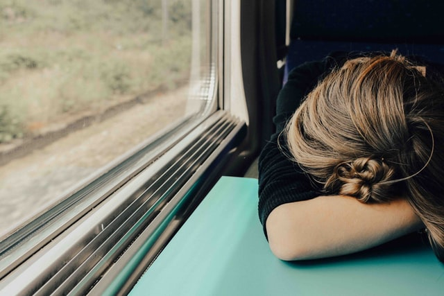 Woman's head on table on a moving train, sleeping