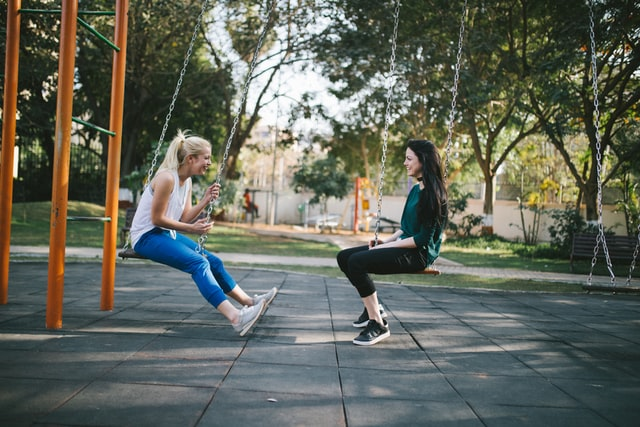 Photo of two white women in a playground sitting on swings side-by-side, facing each other and laughing during a conversation