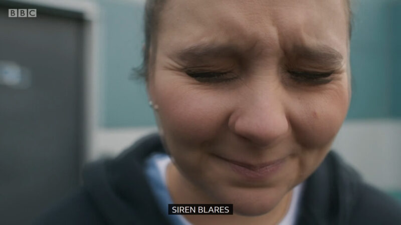 "Clip of a Casualty episode where Jade has her eyes closed, the screen is fuzzy and blurred plus the caption at the bottom is ""Siren blares"""