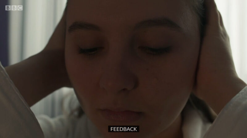 "Clip of Casualty where Jade is putting her hands over her ears and hearing aids, with the caption ""feedback"" at the bottom"