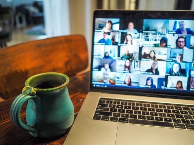 Photo of a mug beside a laptop with an open Zoom video call meeting with over a dozen people's faces blurred