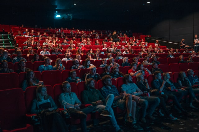 Photo of dozens of people at the cinema sitting in red seats and watching a movie