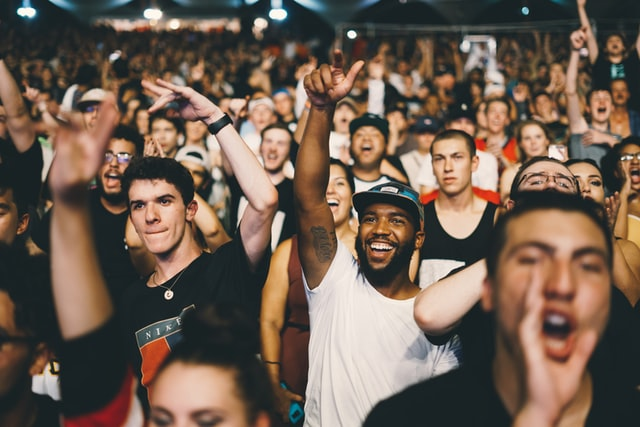 Photo of smiling crowds of people with their hands in the air at a venue
