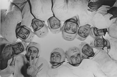 Black and white picture of a dozen white men in classic American football gear, huddled together with the picture taken inside the huddle and looking upwards to the sky and the men