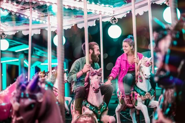 A man and woman holding hands on carousel riding on their own horses