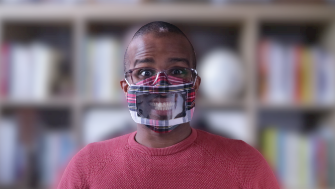Ahmed Khalifa wearing a tartan-coloured clear face-mask and smiling (which you can see)