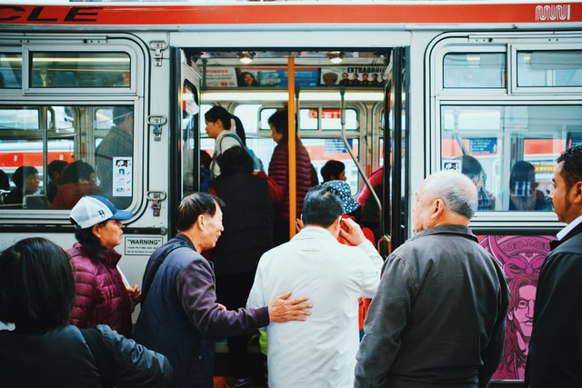 Photo of bus passengers getting on the bus, with one particular passenger placing his hand on another man's back