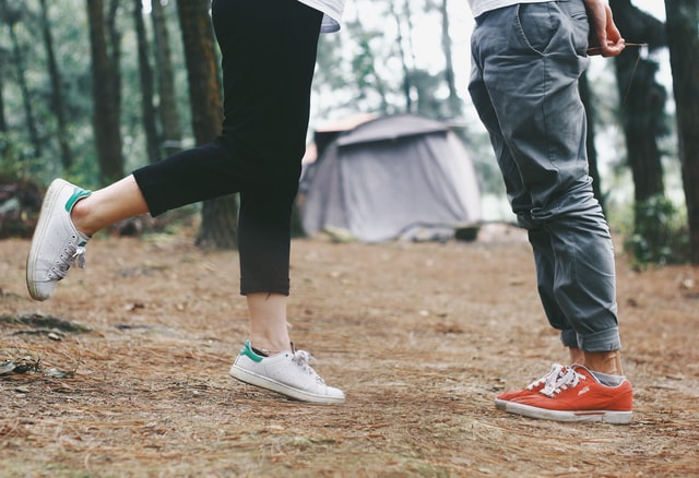 Photo of 2 people's legs, one standing on one leg, the other standing opposite on two feet, with a camp ground in the background