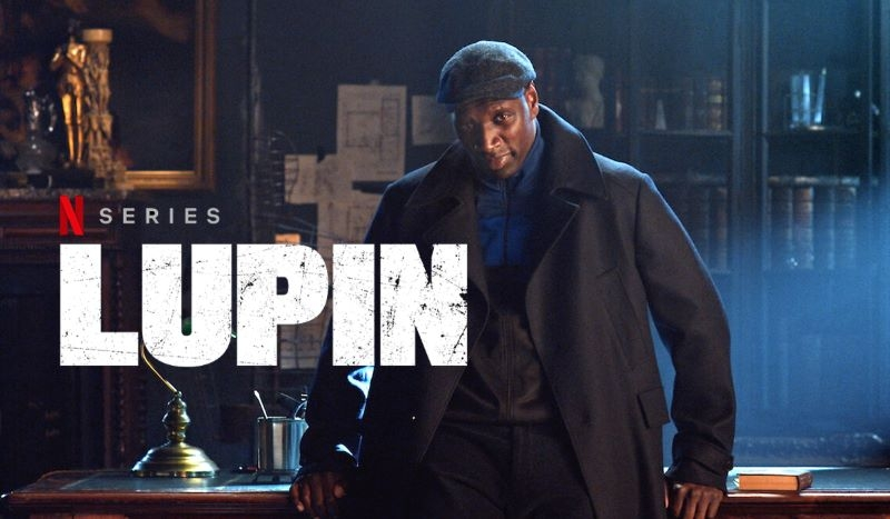 Horizontal picture of Netflix Lupin poster, with Omar Sy sitting on the edge of a desk