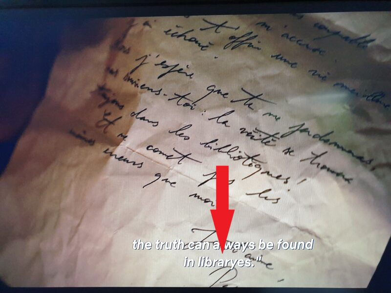 """Grainy picture of a TV showing a scene in 'Lupin' with the subtitles """"the truth can always be found in libraryes"""" and a red arrow pointing to the """"libraryes"""""""