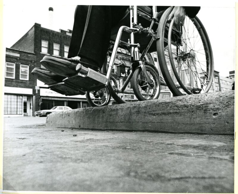 Black and white photo of wheelchair stopped at the end of a drop-down pavement