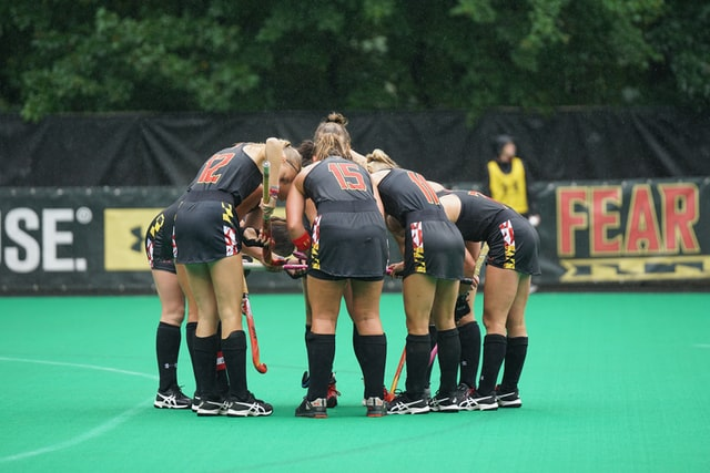 Women hockey players huddling togetherin the middle of the pitch