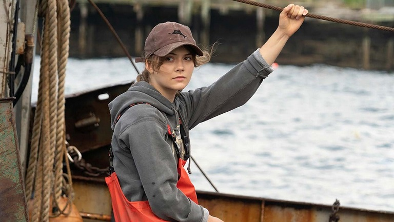 Ruby in the movie 'CODA' sitting in a fishing boat and wearing waterproof gears