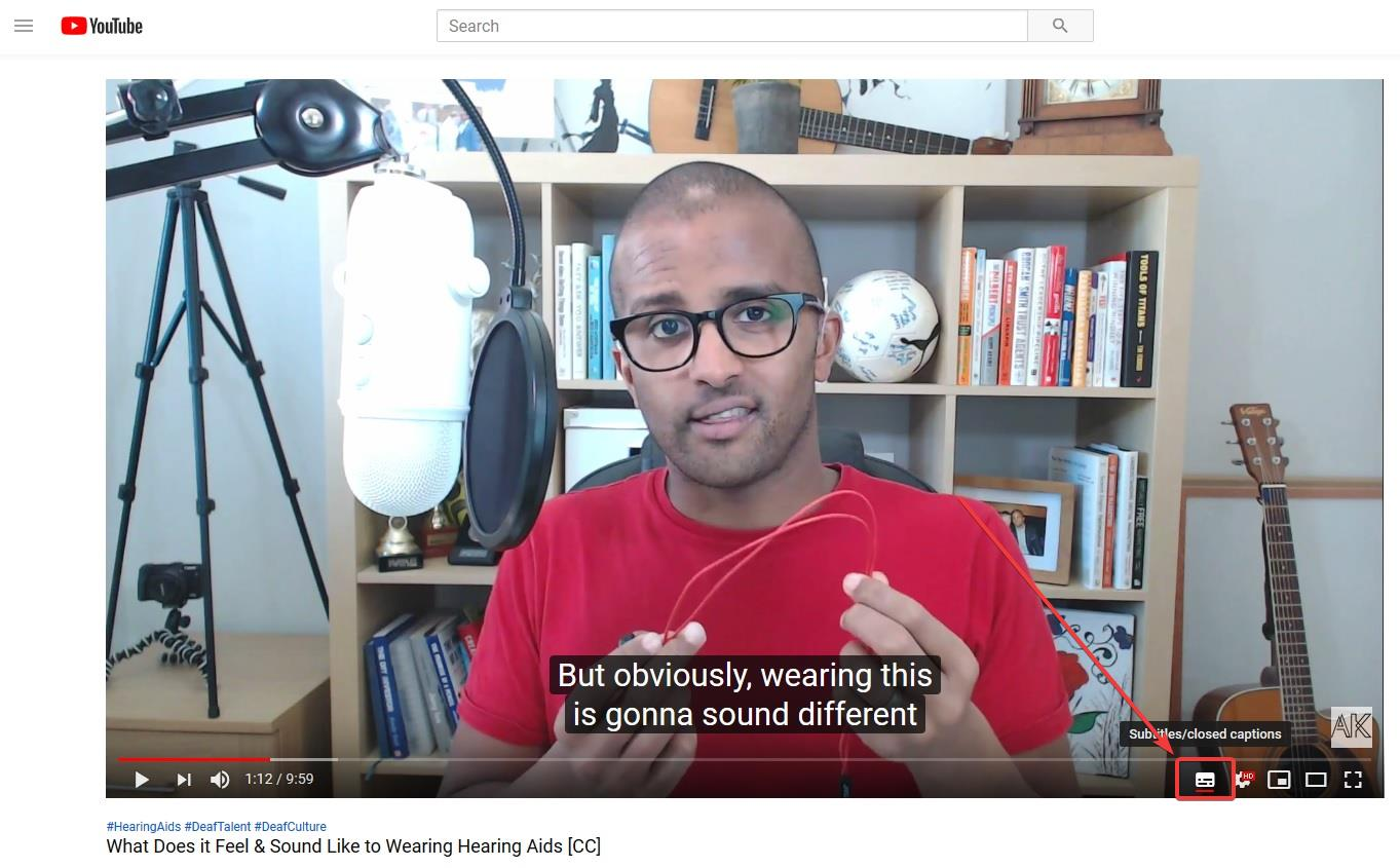 Screenshot of a YouTube video with the arrow pointing to the closed captions feature for switching on