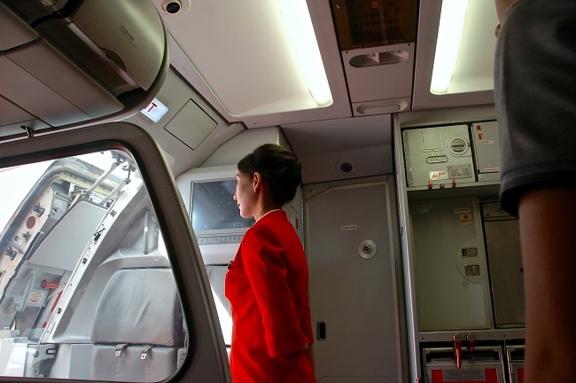 Air stewardess in red outfit waiting inside of an airplane at the door