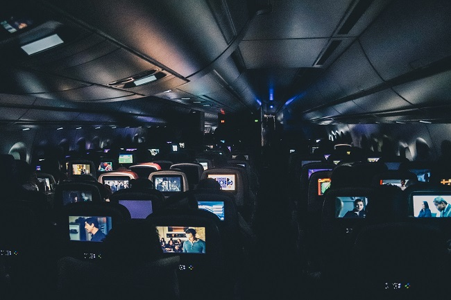 Airplane passengers watching on-flight screens in the dark
