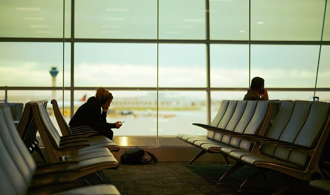 Man and woman sitting separately at an airport departure lounge