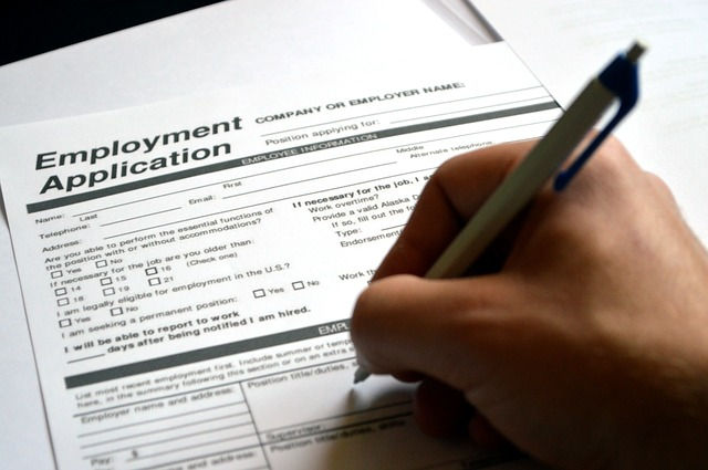 Hand holding a pen filling in an employment application form