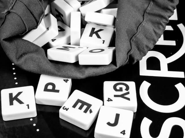 Black and white photo of scrabble pieces poured out of the bag