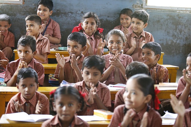 Happy-looking children clapping in classroom