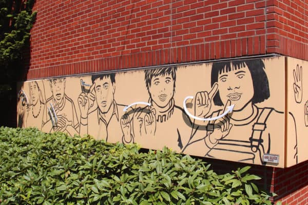 Mural with several ASL signs on the wall of Washington School for the Deaf